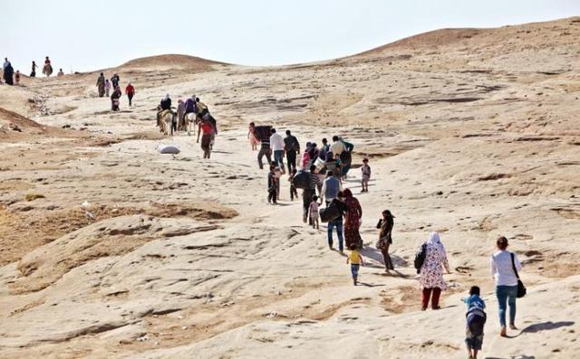 Refugiados sirios caminan con sus pertenencias. ACNUR