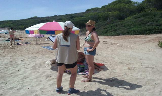 Una turista escucha lo que la 'informadora'  le dice sobre la necesidad de mantener limpias las playas de Mallorca