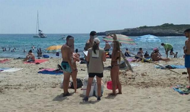 Una informadora apercibe a los turistas de que deben recoger los residuos que generan