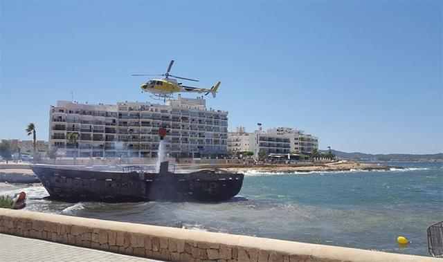 El helicóptero sobrevuela una de los barcos siniestrados tirando agua para apagar el fuego