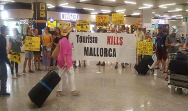Los activistas reciben a los turistas con carteles anti visitantes en el aeropuerto de Pâlma este verano (Archivo)