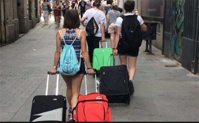 Los turistas arrastran sus trolley hasta llegar a los pisos turísticos que han alquilado
