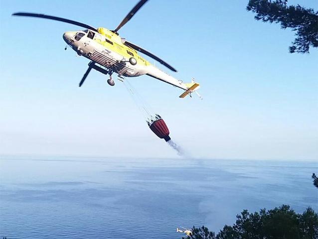Un helicóptero cogiendo agua del mar y transportándola a la zona de Cala Estellencs dónde se ha avivado el fuego (Foto:Ibanat)