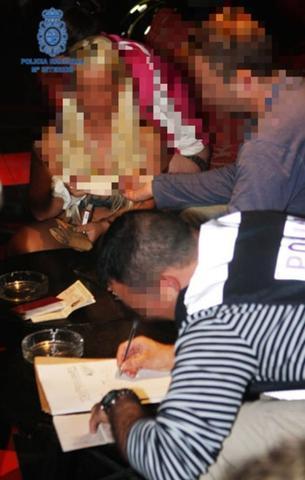 Dos agentes toman datos a una de las 5 mujeres detenidas en el club de alterne