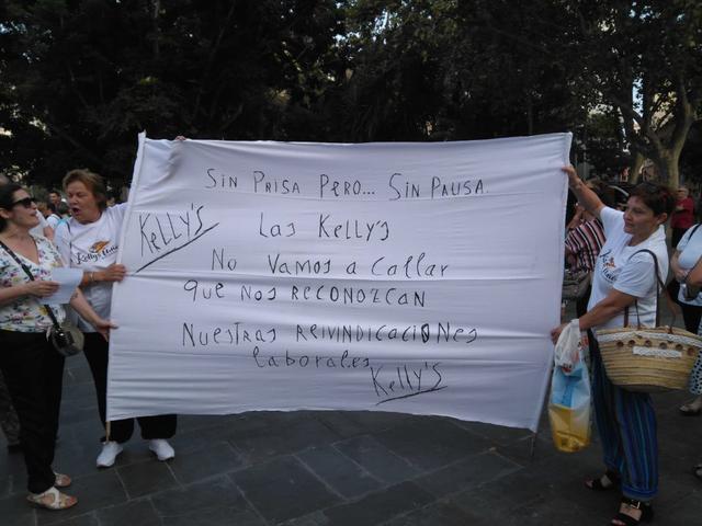 """Dos camareras de pisos con una pancarta en la que se podía leer """"No vamos a callar"""""""