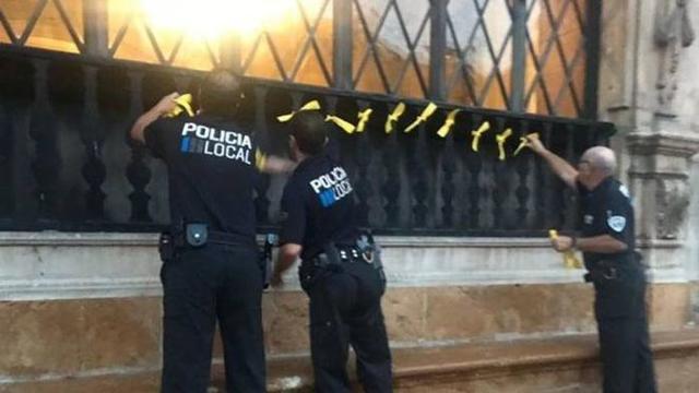 Agentes de la Policía de Palma retira los lazos amarillos con los que amaneció Cort el 1-O