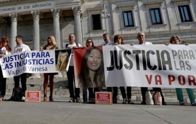 Los familiares de las víctimas mortalmente atropelladas con la pancarta que despleron frente al Congreso de los Diputados
