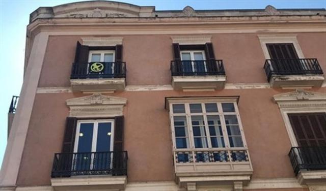 El 'sinsajo' de 'Los Juegos del Hambre' cuelga del balcón de Més en el Parlament (Foto: EP)