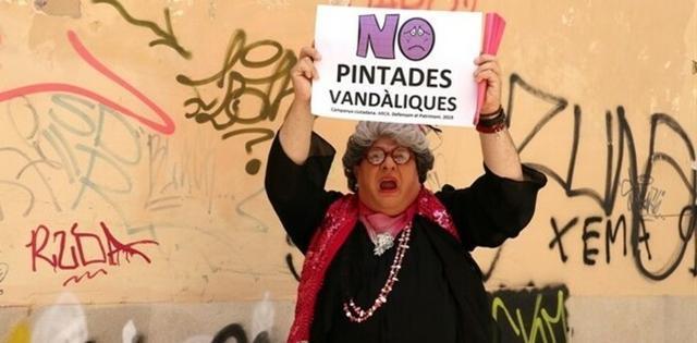 El personaje Madò Pereta, interpretado por Joan Carles Bestard, posa con un cartel en contra de las pintadas vandálicas