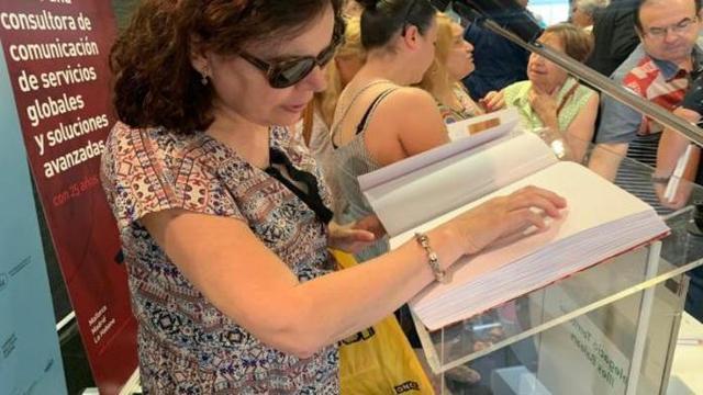 Una mujer ciega lee el libro sobre el 'variat' mallorquí editado por la ONCE (Foto: ONCE)
