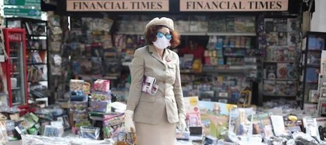 Una mujer protegida con mascarilla y con una revista en su brazo posa al lado de uno de los quioscos de Madrid (Foto: EP)